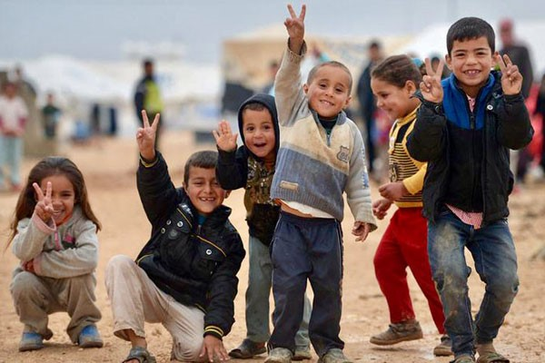 "Refugee children wave and flash the ""peace"" sign"