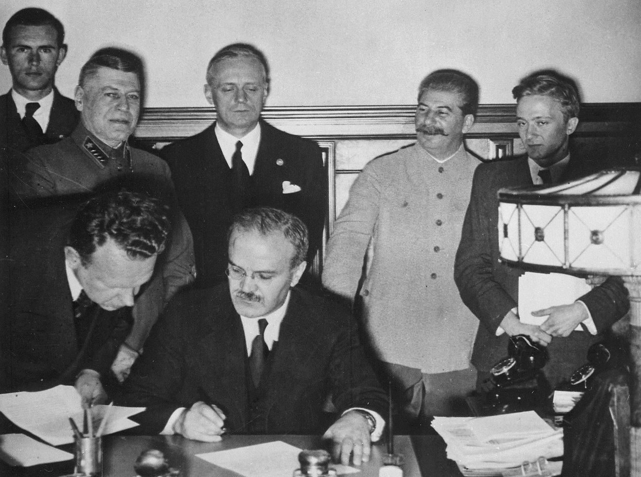 Soviet Foreign Commissar Vyacheslav Molotov signs the German-Soviet nonaggression pact; Joachim von Ribbentrop and Josef Stalin stand behind him. Moscow, August 23. 1939.