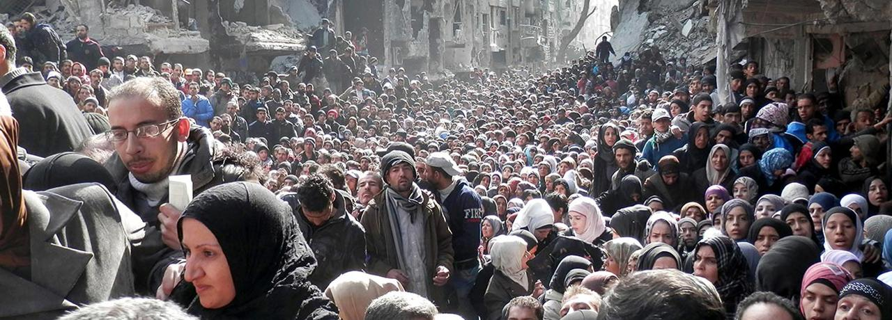 Palestinian refugees line up for food at Yarmouk refugee camp in Damascus, Syria.