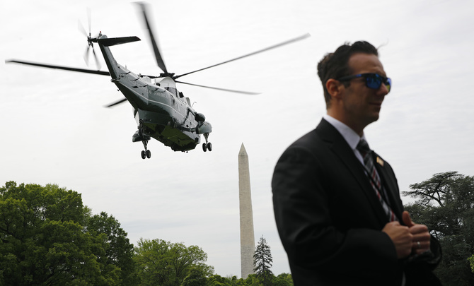 Marine One, with President Donald Trump aboard, lifts off above a member of the U.S. Secret Service