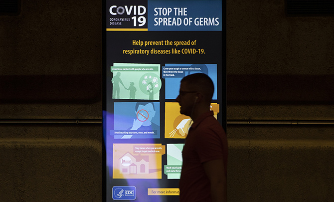 A commuter walks past a video display on the Gallery Place Metro subway train platform in Washington, Friday, March 13, 2020, with a message from the Centers for Disease Control and Prevention (CDC) on the how to combat the coronavirus outbreak.