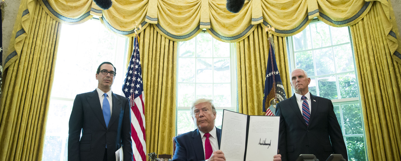 In this June 24, 2019, file photo, President Donald Trump holds up a signed executive order to increase sanctions on Iran, in the Oval Office of the White House in Washington, with Treasury Secretary Steven Mnuchin, left, and Vice President Mike Pence.