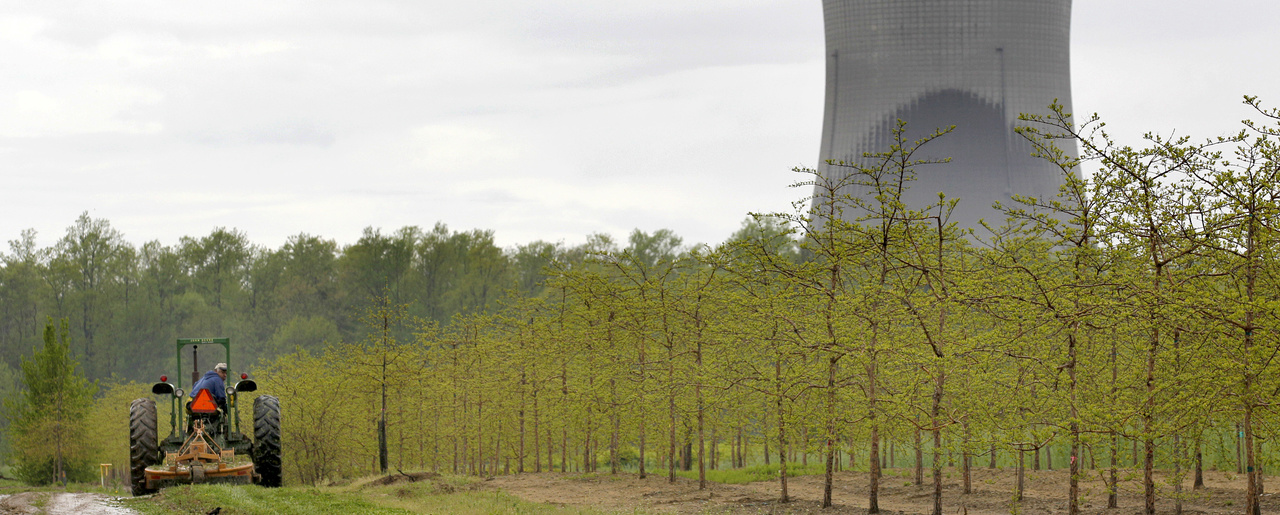 A worker drives a tractor near the cooling towers of the Perry Nuclear Power Plant looming in the background in North Perry, Ohio, on May 18, 2011.