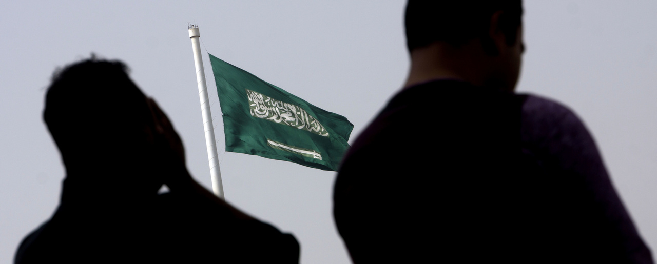 People pray at an open air makeshift mosque in front of a giant Saudi Flag in Jiddah, Saudi Arabia, Wednesday, June 21, 2017. Saudi Arabia's King Salman on Wednesday appointed his 31-year-old son Mohammed bin Salman as crown prince. (AP Photo/Amr Nabil)