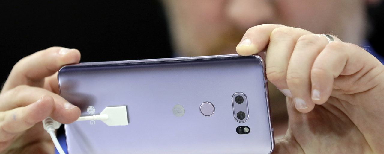 A man holds the new LG V30 smartphone at a tech fair in Berlin on August 31, 2017. U.S. government statistics that paint a grim picture of wage growth do not account for the benefits that technological progress, including the invention of the smartphone, have for consumers, Martin Feldstein argues. (AP Photo/Michael Sohn)