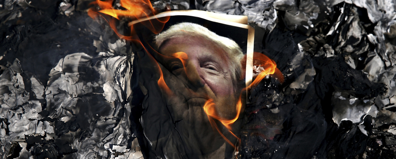 A portrait of U.S. President Donald Trump is set on fire by Iranian mourners during the state funeral of Mohsen Hojaji, a young Revolutionary Guard soldier beheaded by the Islamic State group in Syria, Wednesday, Sept. 27, 2017, in Tehran, Iran. (AP Photo/Ebrahim Noroozi)