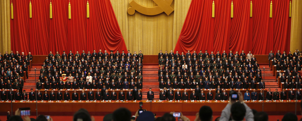 Journalists take pictures of Chinese President Xi Jinping, front row center, and his cadres stand for the Communist song during the closing ceremony for the 19th Party Congress at the Great Hall of the People in Beijing on Oct. 24, 2017 (AP Photo/Andy Wong).