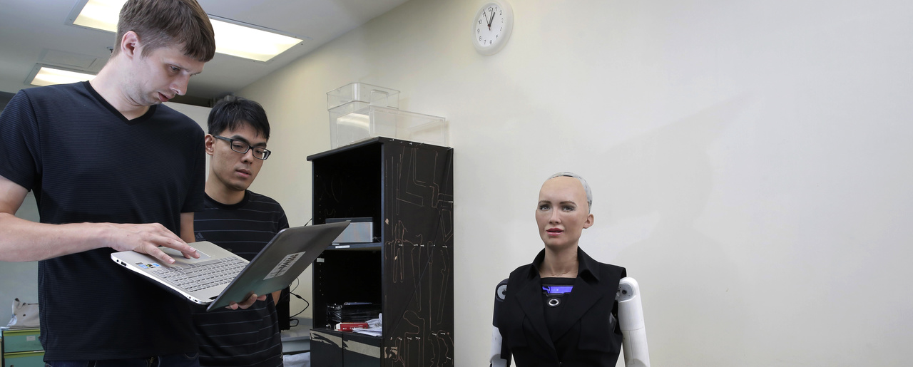 Staff members of Hanson Robotics control their company's flagship robot Sophia, a lifelike robot powered by artificial intelligence in Hong Kong. September 28, 2017 (Kin Cheung/Associated Press).