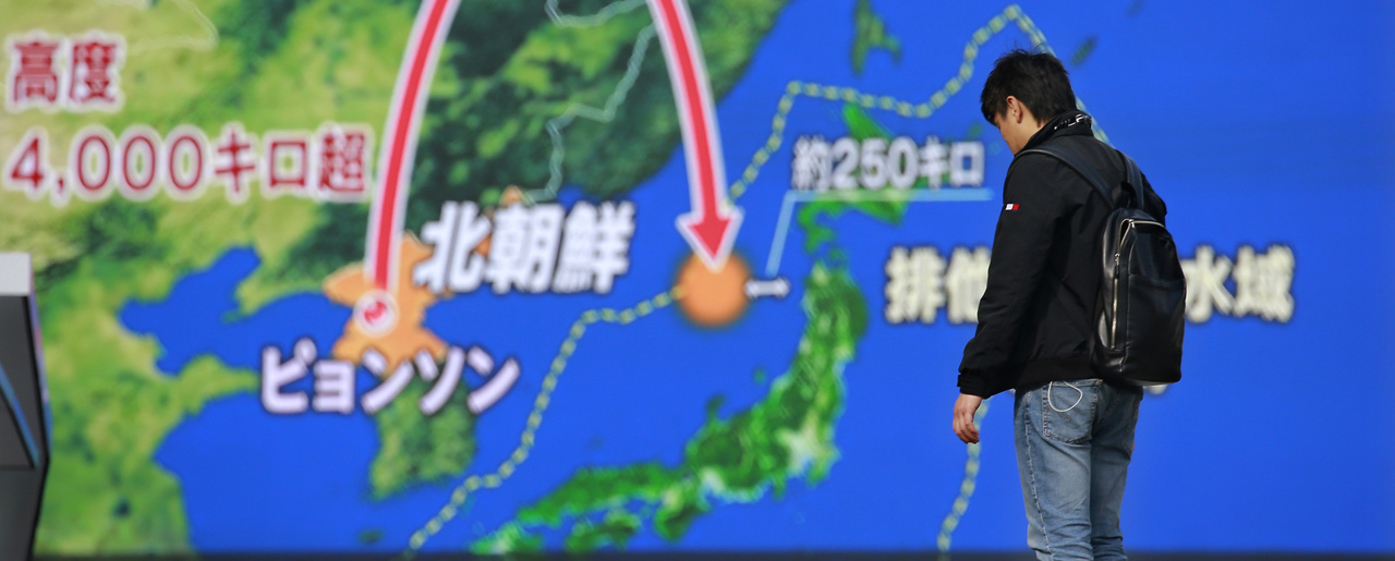 Photo of a man standing in front of a screen showing a TV program image regarding a North Korea's missile launch.