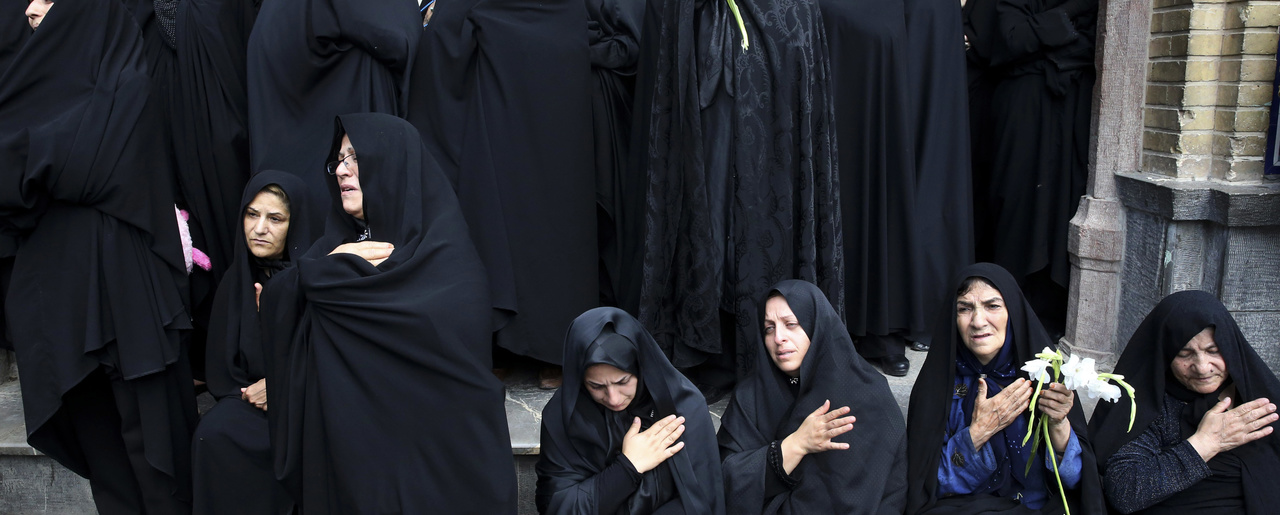 In this June 25, 2015 file photo, Iranian women mourn during the funeral ceremony of Ali Amraei and Hassan Ghaffari, who were killed in fighting against Islamic State extremists in Syria, in southern Tehran, Iran. The protests that broke out in late December 2017 across Iran predominantly involve economic issues, but demonstrators also say the government is sending its young men to fight and die in Syria and spending billions of dollars on the military when it should be focused on providing jobs in Iran.