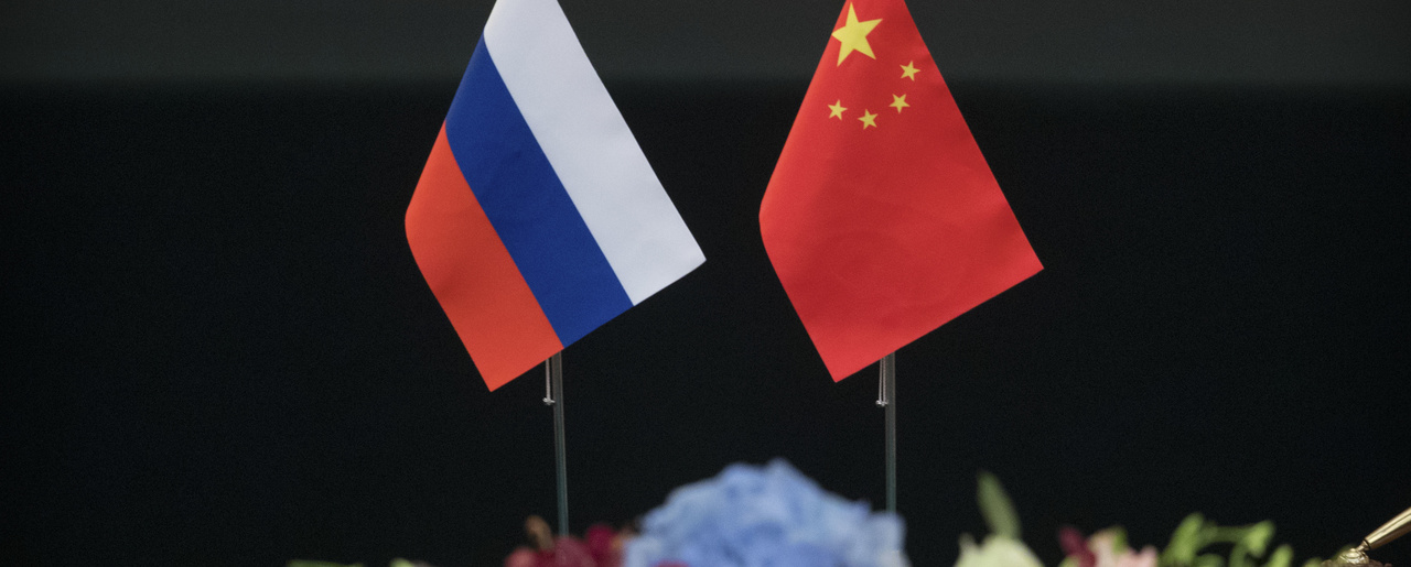 Russian and Chinese flags sit side by side on a table in the Great Hall of the People, Beijing, on June 8, 2018.