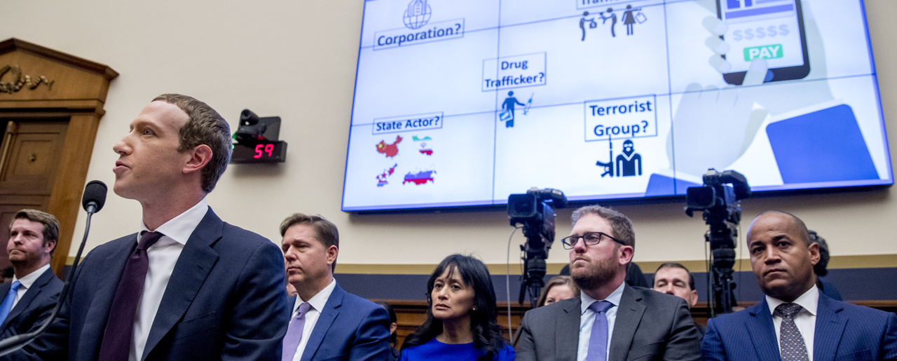 """The words """"If Consumers Use Libra, Who Would They Be Dealing With?"""" is displayed on a monitor behind Facebook CEO Mark Zuckerberg as he testifies before a House Financial Services Committee hearing on Capitol Hill in Washington, Wednesday, Oct. 23, 2019, on Facebook's impact on the financial services and housing sectors."""