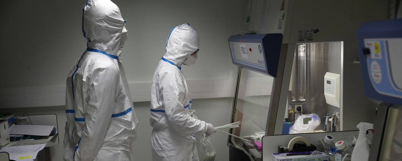 French lab scientists in hazmat gear inserting liquid in test tube manipulate potentially infected patient samples at Pasteur Institute in Paris.