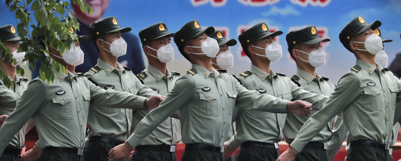 Photo of Chinese People's Liberation Army (PLA) soldiers wearing face masks to protect against the spread of the new coronavirus march past a banner depicting Chinese President Xi Jinping at their living squatter inside the Tiananmen Gate in Beijing during a plenary session of China's National People's Congress (NPC) at the Great Hall of the People in Beijing, Monday, May 25, 2020.
