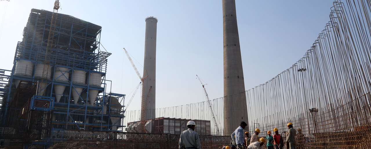 Workers lay cement to build a concrete structure at a coal-fired power plant