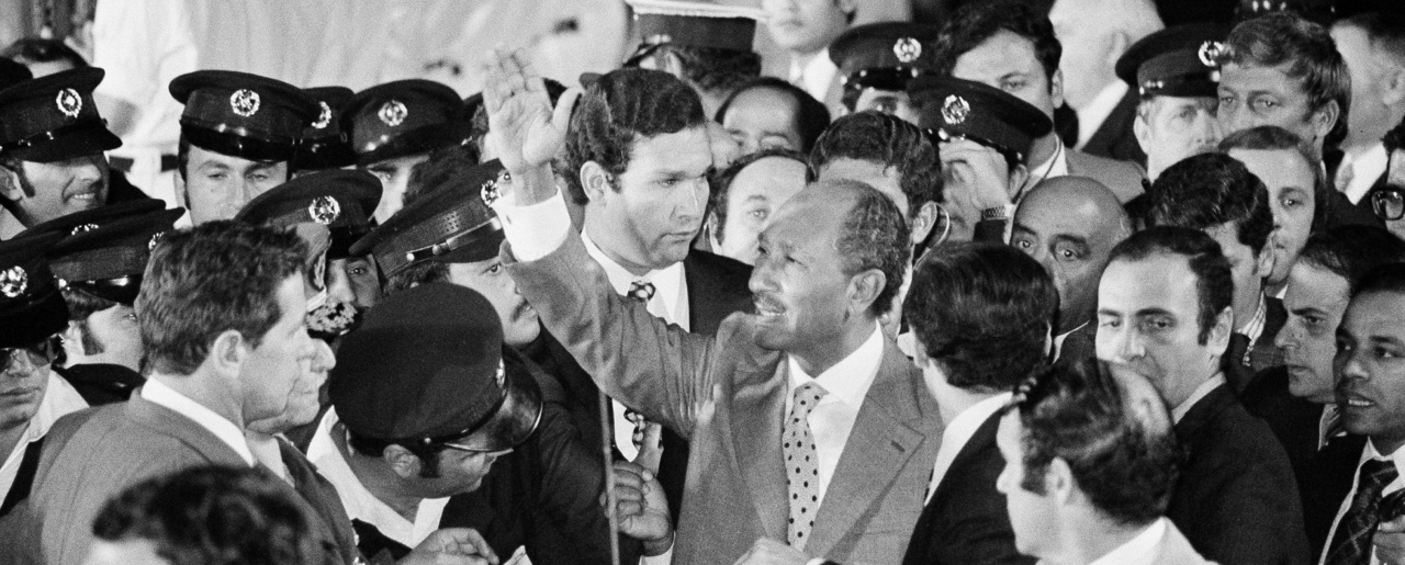 Egyptian President Anwar Sadat is surrounded by security people as he waves to cheering crowds just before he leaves Ben Gurion Airport for Jerusalem, Nov. 19, 1977.