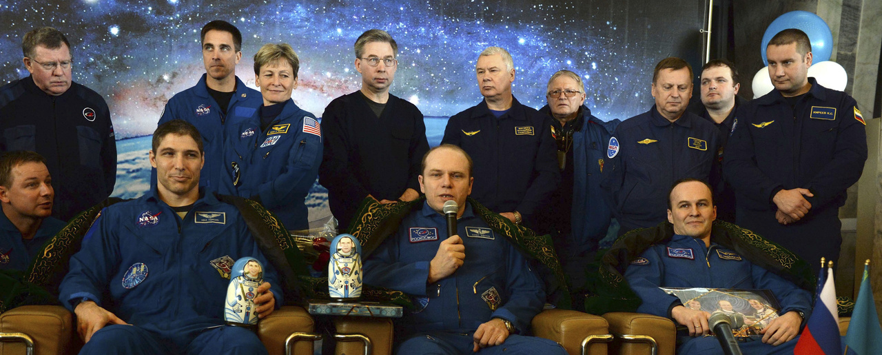 Wearing traditional Kazakh costumes on the shoulders, from left, U.S. astronaut Michael Hopkins and Russia's cosmonauts Oleg Kotov and Sergey Ryazansky attend a press conference in Karaganda, Kazakhstan, Tuesday, March 11, 2014, shortly after their landing aboard Soyuz TMA-10M capsule. Hopkins together with the two Russia's cosmonauts landed safely in the Kazakh steppe aboard a Russian Soyuz capsule after a stay of over five months aboard the International Space Station. (AP Photo/Vasily Maximov, pool)