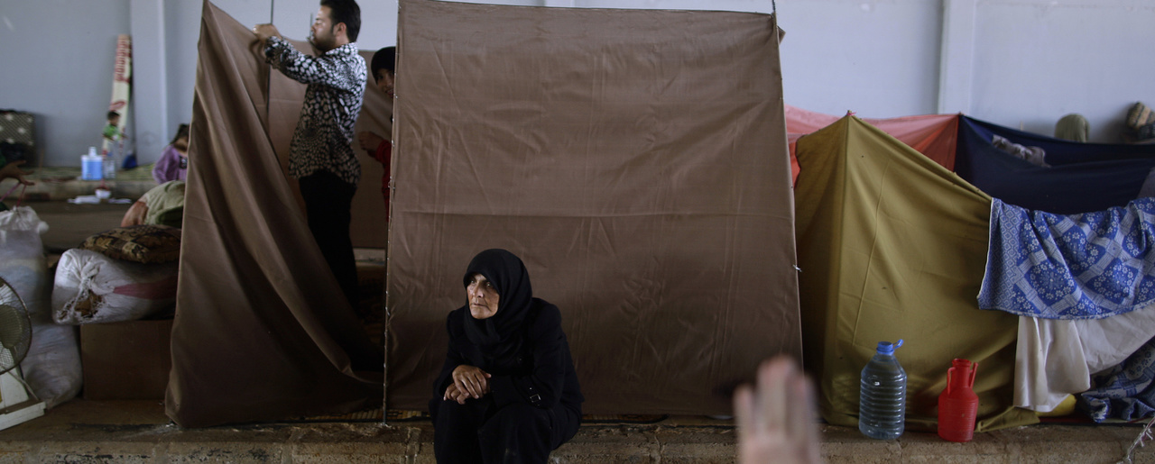 A Syrian woman, who fled her home in Aleppo due to government shelling, rests while her son constructs a makeshift tent made of sheets, as they take refuge at Bab Al-Salameh crossing border, hoping to cross to one of the refugee camps in Turkey, near the Syrian town of Azaz, Thursday, Sept. 13, 2012.