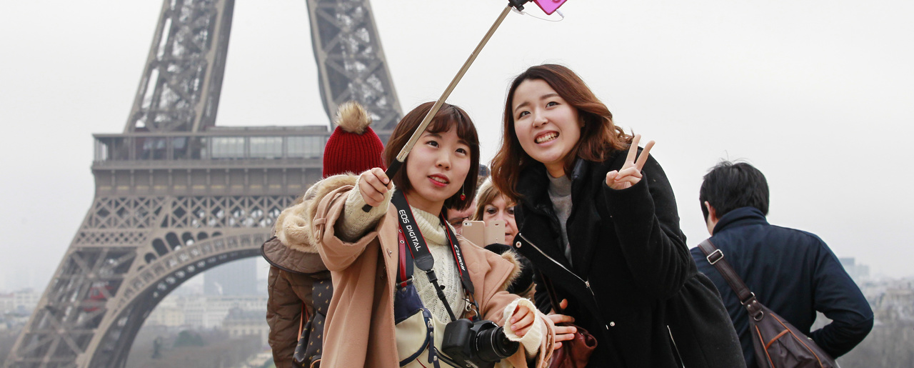 Chinese Tourists taking pictures in front of the Eiffel tower.