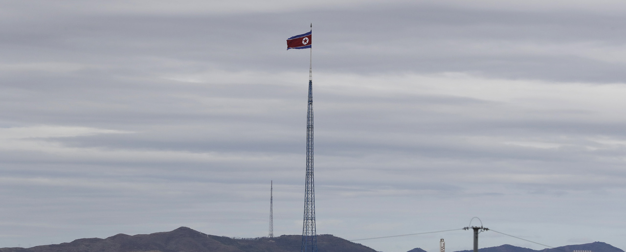 A North Korean flag flutters in the wind atop a 160-meter tower