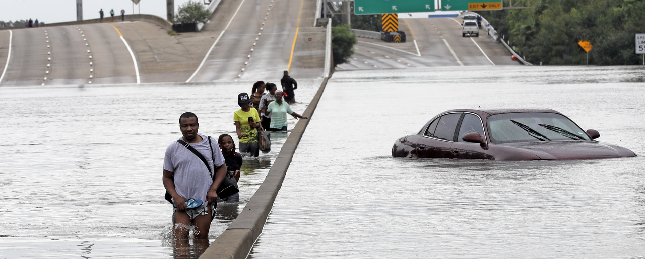 Evacuees wade down a flooded section of Interstate 610 in Houston