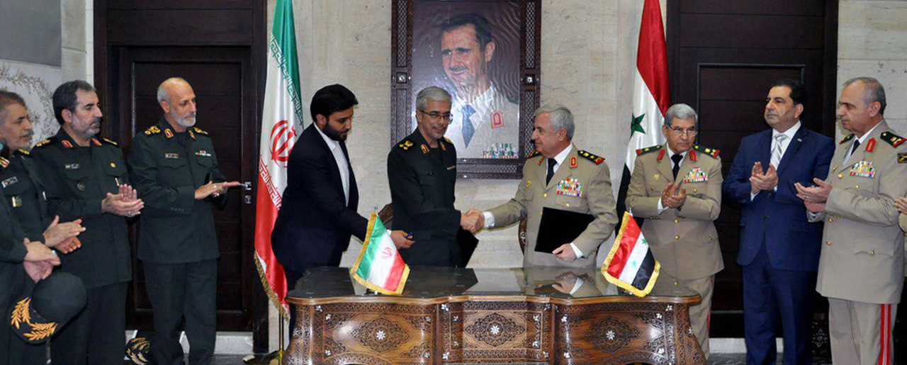 Chief of Staff of Iran's armed forces, Maj. Gen. Mohammad Bagheri, center left, shakes hands with his Syrian counterpart Gen. Ali Ayoub, center right, during a ceremony to sign a joint memorandum of understanding for developing cooperation and coordination between the two countries' armies in Damascus