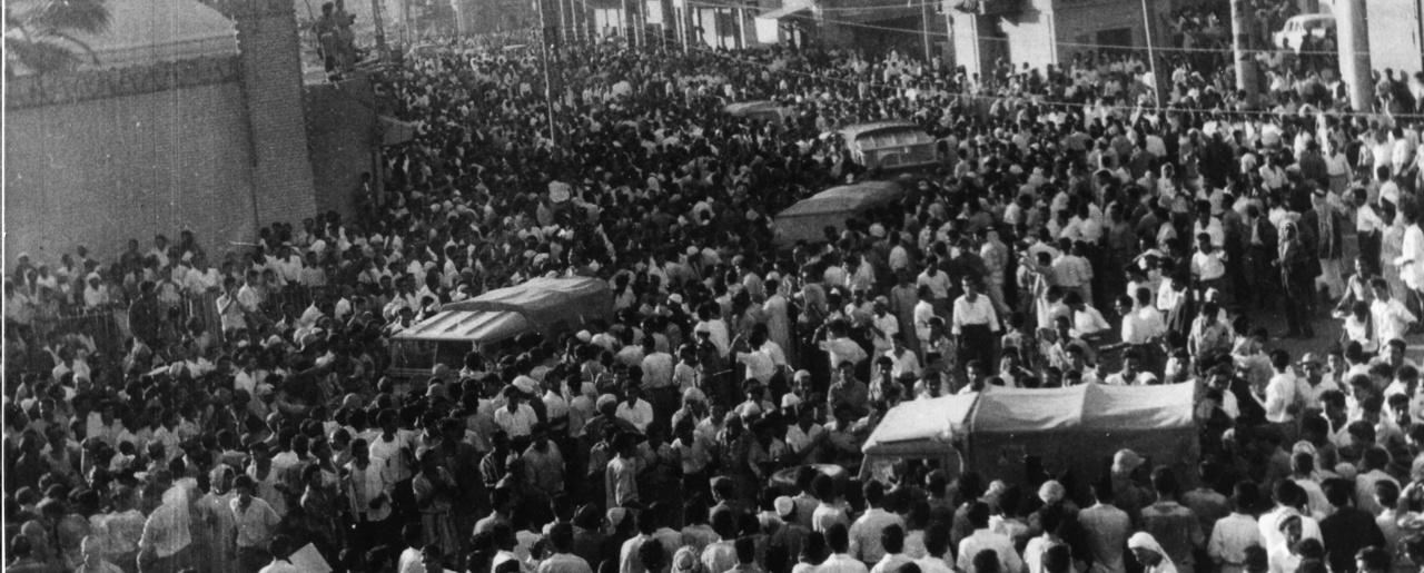 Military vehicles move slowly through the crowded streets in Baghdad, Iraq, July 14, 1958.