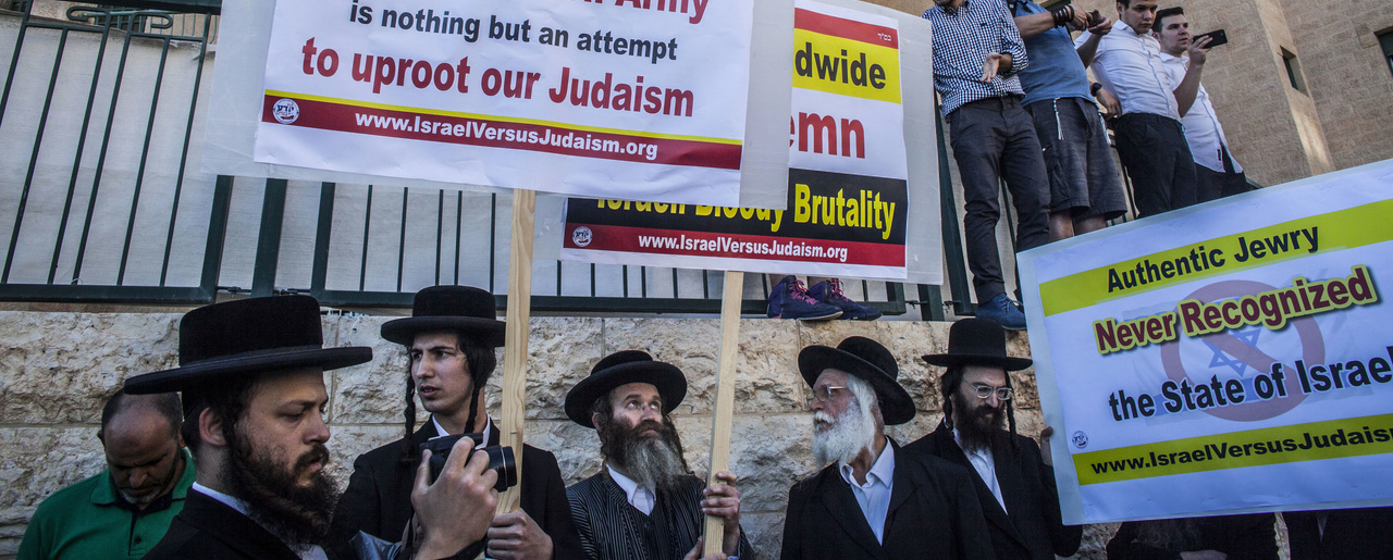 ultra-Orthodox Jewish men wave signs