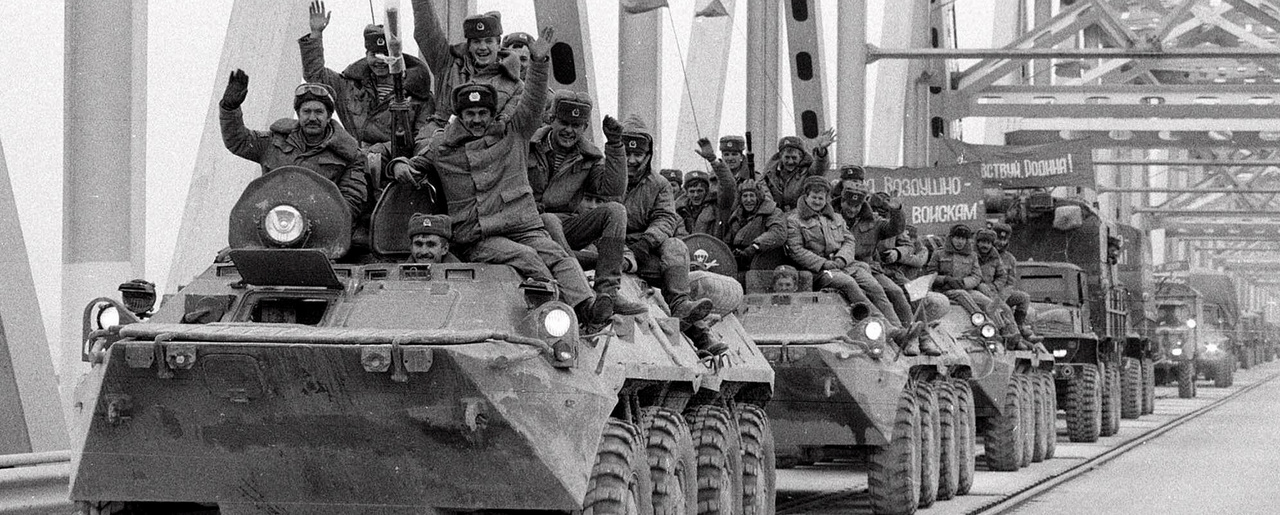 Soviet Army soldiers wave their hands as their last detachment crosses a bridge on the border between Afghanistan and then Soviet Uzbekistan