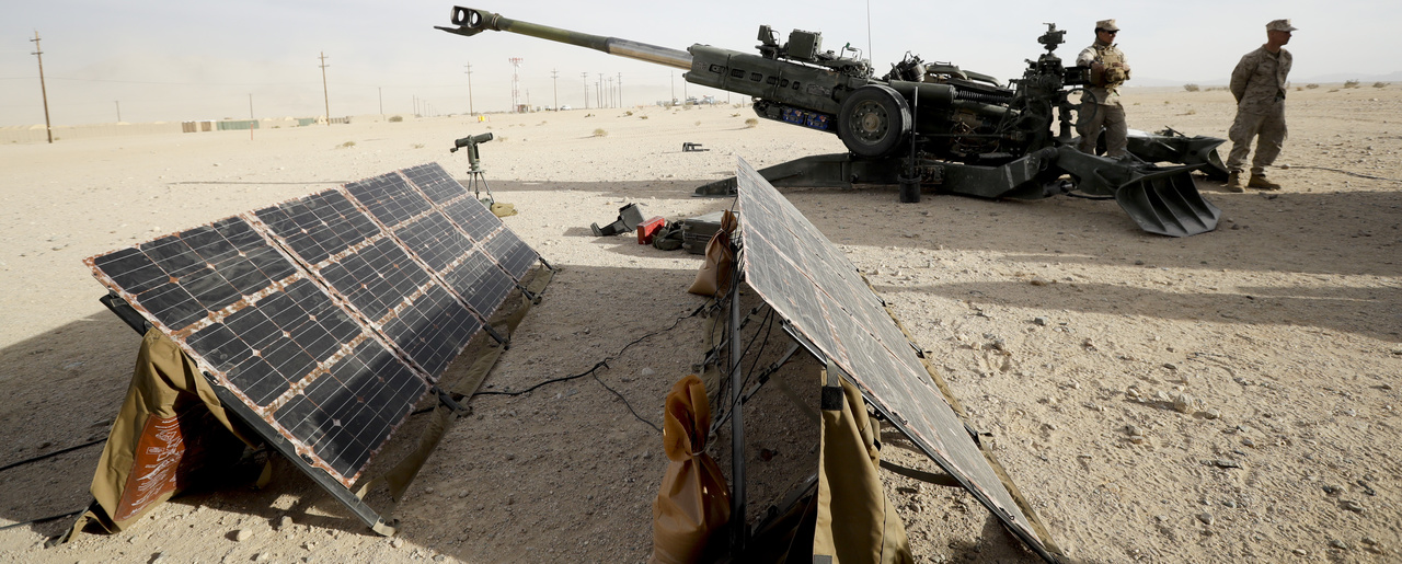Marines stand near an artillery piece that links to solar panels during an exhibition of green energy technology in Twentynine Palms, Calif.