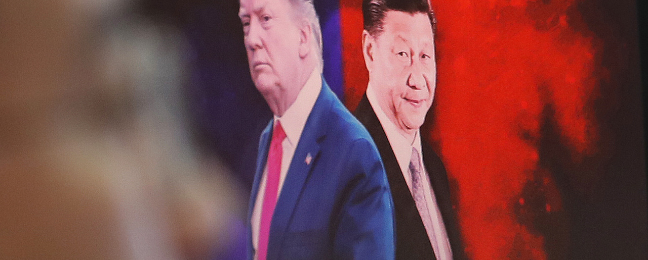 a computer screen shows images of Chinese President Xi Jinping, right, and U.S. President Donald Trump as a currency trader works