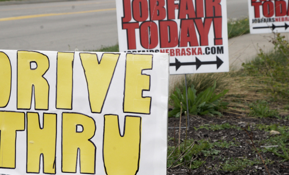 In this Wednesday, May 6, 2020, photo, signs point to a drive-thru job fair in Omaha, Neb.