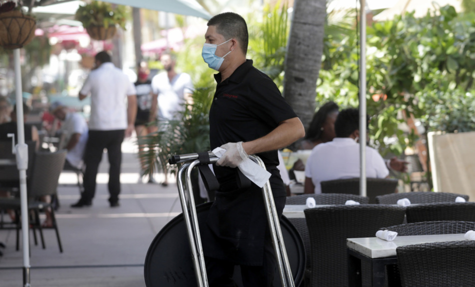 In this July 12, 2020, file photo, a waiter wears a protective face mask and gloves while working at the il bolognese restaurant along Ocean Drive during the coronavirus pandemic, in Miami Beach, Fla. Unemployment remains painfully high in the U.S. even as economic activity is slowly picking up.