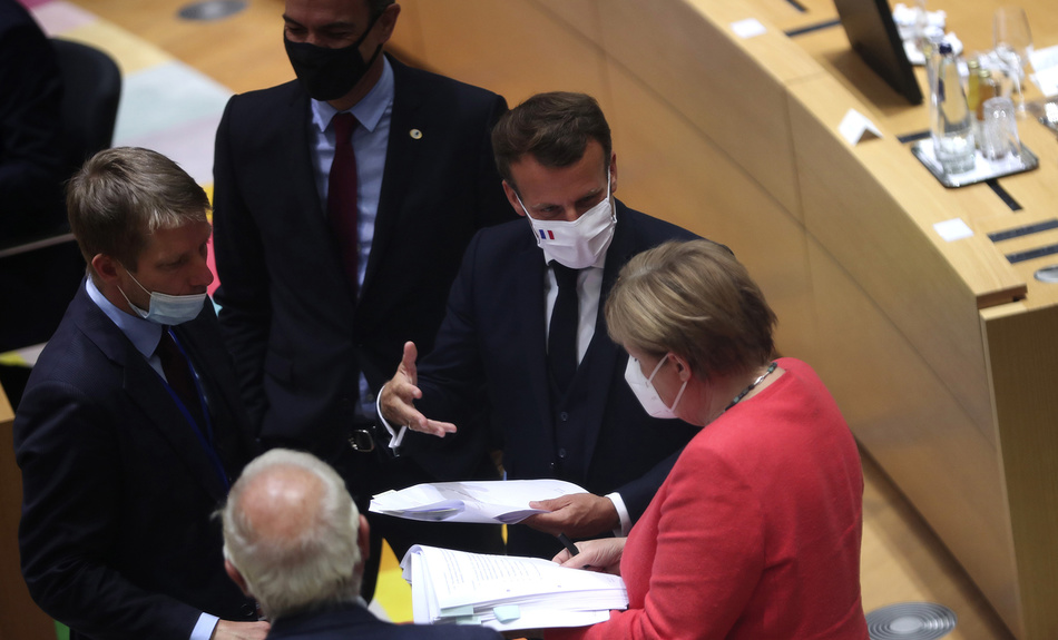 French President Emmanuel Macron, second right, looks over papers with German Chancellor Angela Merkel, right, during a round table meeting at an EU summit in Brussels, Monday, July 20, 2020.