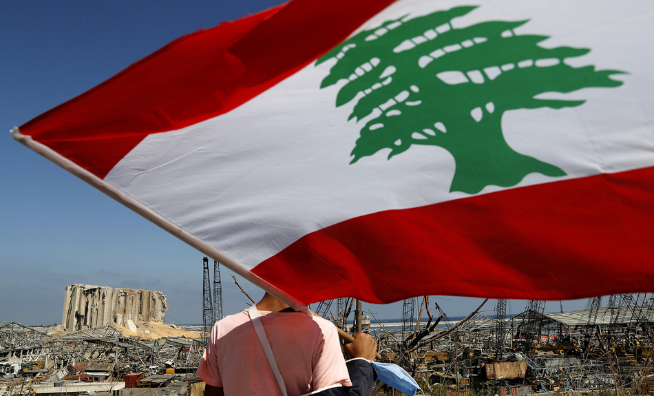 A man holds the Lebanese flag, as he looks at the scene of Tuesday's explosion that hit the seaport of Beirut, Lebanon, Friday, Aug. 7, 2020.