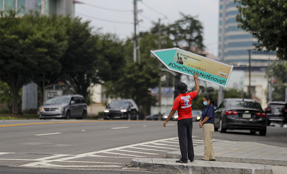 John Miller, 25, of Atlanta, spins a large check sign for the #OneCheckIsNotEnough campaign near Georgia Sen. David Perdue's office on Tuesday, Aug. 11, 2020, in Atlanta.