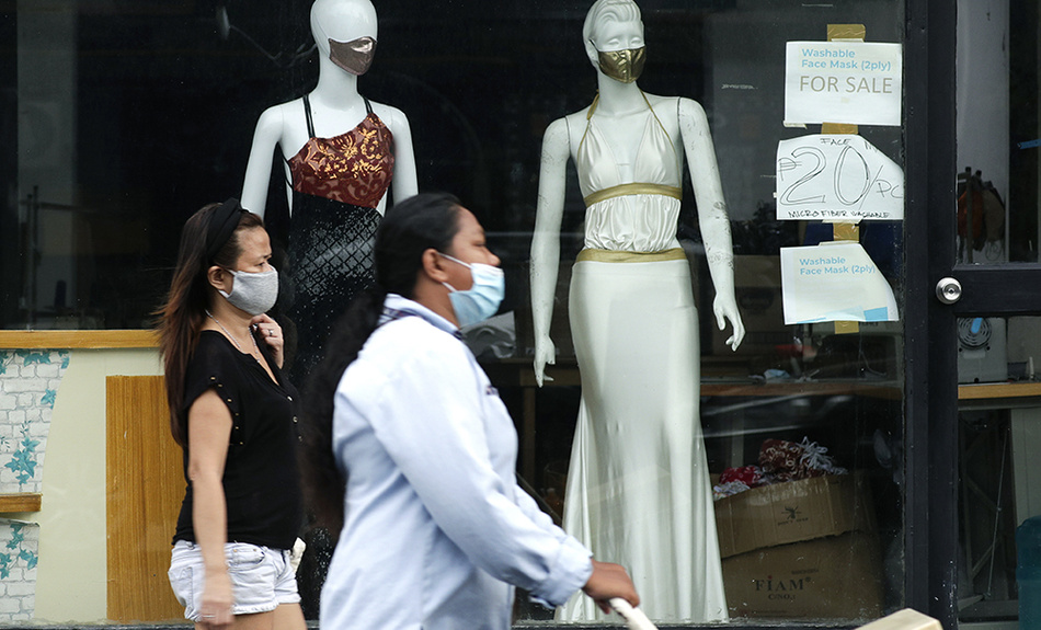 Women walk past mannequins wearing face masks advertised for sale, at a shop in Makati city, Philippines, Tuesday, Sept. 29, 2020.