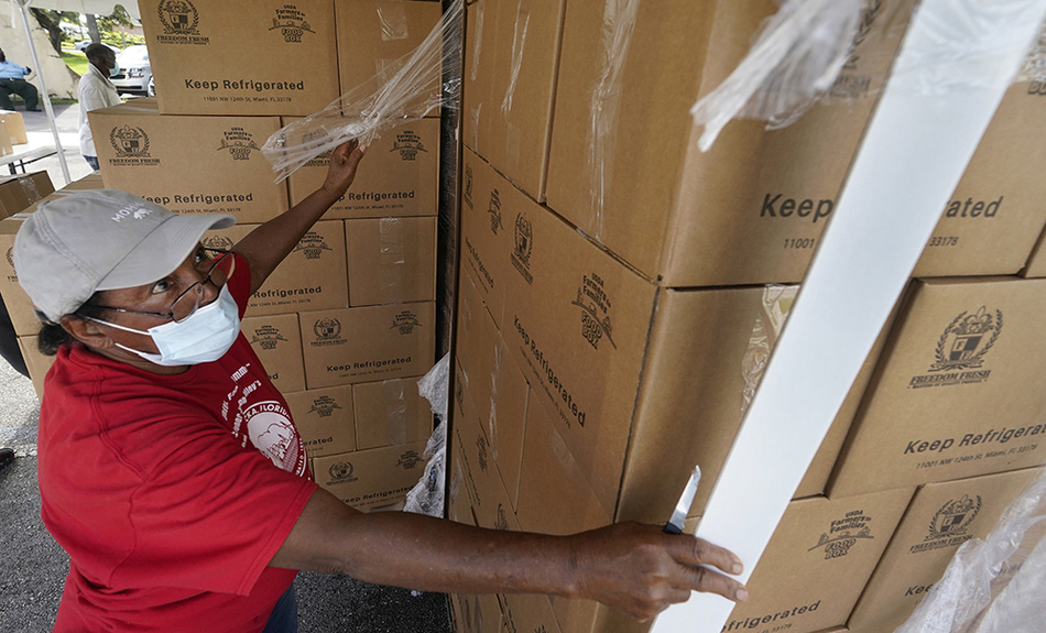 Volunteer Mary Jenkins opens pallet-loads of food to be given out at a food distribution event, Tuesday, Oct. 6, 2020, in Opa-locka, Fla. The drive-thru food distribution was hosted by Feeding South Florida. Shutdowns and restrictions have battered Florida's economy, leaving hundreds of thousands unemployed in the tourist-dependent state.