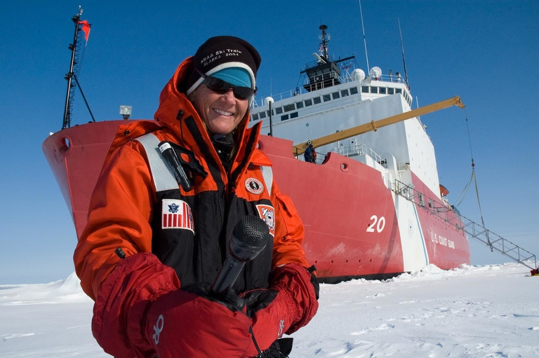 Elizabeth Aronld stands on the sea ice in front of a Russian icebreaker.