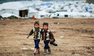 Syrian boys, whose family fled their home in Idlib, walk to their tent at a camp for displaced Syrians in Atmeh, Syria, Dec. 10, 2012 - Alex Rondu, Freedom House