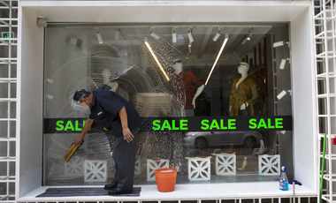 An employee cleans a store window in Mexico City, Thursday, July 30, 2020. Mexico's economic activity plummeted 18.9% in the second quarter compared to the same period last year as the economic shutdown caused by the COVID-19 pandemic drove the country deeper into a recession.
