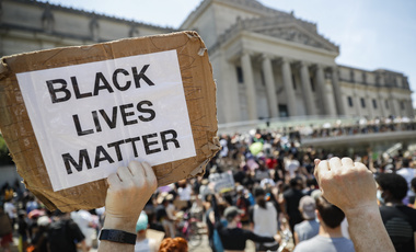 "In this June 19, 2020, file photo, a protester holds a sign that reads ""BLACK LIVES MATTER"" during a Juneteenth rally outside the Brooklyn Museum in the Brooklyn borough of New York."