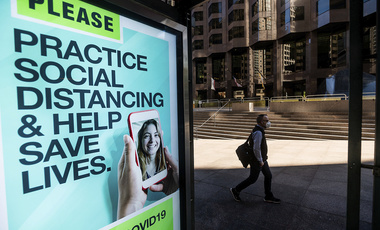 A man passes a COVID-19 public service notice in San Francisco's financial district on Wednesday, Oct. 21, 2020.