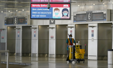 In this Sept. 30, 2020, file photo, an employee walks through an empty American Airlines arrivals area at Miami International Airport during the coronavirus pandemic in Miami.