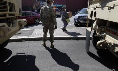 A Massachusetts National Guard soldier, from the 181st Engineer Company, center, and a woman carrying a box of food distributed by the National Guard, right, wear masks out of concern for the coronavirus, Tuesday, May 5, 2020, in Chelsea, Mass.