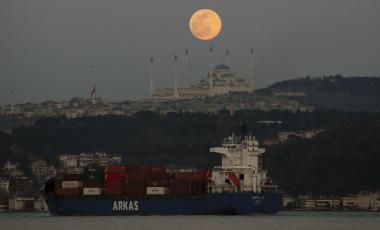 The full moon rises over the sky in Istanbul, Sunday, March 28, 2021, with a view of the Camlica Mosque, the largest mosque in Asia Minor as a ship crosses the Bosphorus Strait separating European and Asian sides of the metropolis.