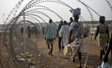 In this Tuesday Jan. 19, 2016 file photo, displaced people walk next to a razor wire fence at the United Nations base in the capital Juba, South Sudan.