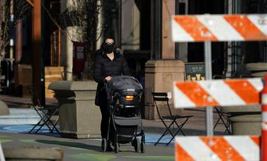 A woman wears a face covering while pushing a stroller along Larimer Street while navigating the shops and restaurants open in Larimer Square late Friday, Feb. 5, 2021, in lower downtown Denver.