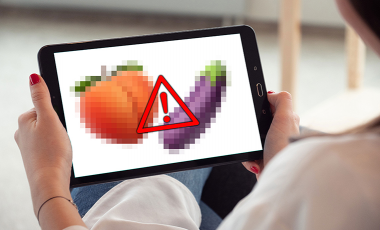 A woman views a peach and eggplant emoji on her tablet