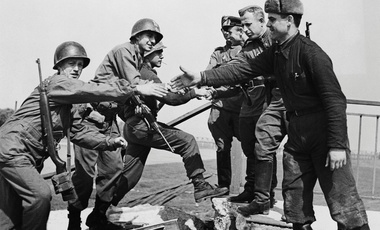 US troops of the 69th Infantry Division (left), shake hands with Russian troops in a staged photo on the wrecked bridge over the Elbe at Torgau, Germany, to mark the previous day's link-up between American and Soviet forces, 26th April 1945. Among the Americans are Bernard E. Kirschenbaum and Richard Johnson (second and third from left, respectively).